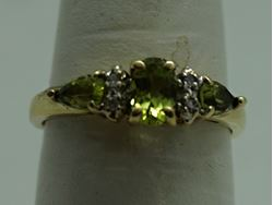 Picture of 10KT YELLOW GOLD RING WITH  4 DIAMONDS 0.02PTS AND 3 PERIDOTS  (1 OVAL; 2 PEAR SHAPE).1.8GR SIZE 7.25 VERY GOOD CONDITION. PRE OWNED.