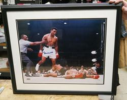 """Picture of """" MUHAMMAD ALI KNOCKS OUT SUNNY LISTON"""" . AUTOGRAPHED. FRAME SIZE 22X25 . PICTURE SIZE 19X22. WITH GRANDSTAND SPORT HOLOGRAM, ONLINE AUTHENTIC HOLOGRAM ."""